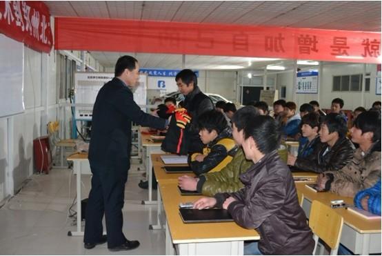 校长刘振华在开班仪式上为北方新学员发放北方校服.jpg